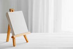 Empty canvas on easel on white desk. Empty canvas on easel on white wooden desk stock photography