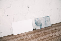 Empty canvas in room. Side view of empty white and polygonal canvas leaning on wall in brick interior with wooden floor. Mock up, 3D Rendering Royalty Free Stock Images