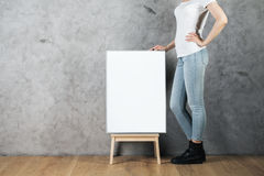 Empty canvas on stool. Woman with empty canvas on stool standing in room with concrete wall and wooden floor. Advertising concept. Mock up Royalty Free Stock Photos
