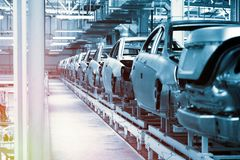 Car bodies are on Assembly line. Factory for production of cars in blue. Modern automotive industry. Blue tone. Empty car bodies are on production line stock photography