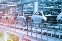 Car bodies are on Assembly line. Factory for production of cars in blue. Modern automotive industry. Blue tone. Empty car bodies are on production line stock photo