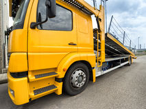 Empty car carrier truck. Yellow car carrier truck with raised ramp Royalty Free Stock Image