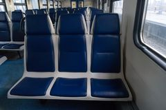 Empty car of electric train. With blue soft seats in day Royalty Free Stock Image