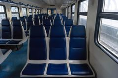 Empty car of electric train. With blue soft seats at day Stock Image