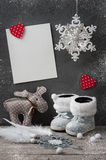 Empty card and christmas decorations. White empty card on concrete wall with burning candle and christmas decorations. Space for greeting text Royalty Free Stock Photos
