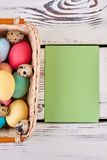 Empty card and easter basket. Paper on white wood background. Send Easter greetings Royalty Free Stock Photo