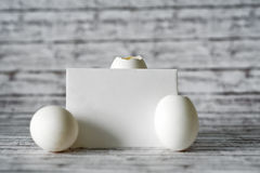 Empty Card with Three White Eggs on a Table Royalty Free Stock Photos