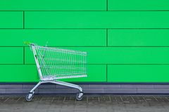 The empty cart, against the background of a green wall. Sales, discounts. A basket for products stock images