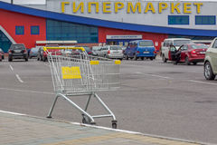 An empty cart with a view of the sign of the hypermarket Royalty Free Stock Image