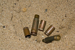 Empty cartridges on sand. Empty sleeves from a pistol and the automatic machine on sand close up. Shallow DOF stock photography