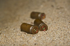 Empty cartridges on sand. Empty sleeves from a pistol on sand close up. Shallow DOF royalty free stock images