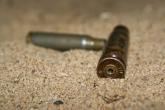 Empty cartridges on sand Royalty Free Stock Photography