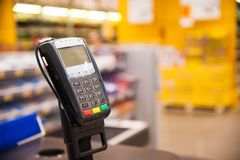 Cash desk with payment terminal in supermarket. Empty cash desk with payment terminal and customers in queue in supermarket Royalty Free Stock Image