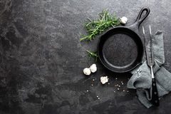 Empty cast iron frying pan on dark grey culinary background, view from above Royalty Free Stock Photo