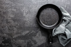 Empty cast iron frying pan on dark grey culinary background, view from above. Copy space royalty free stock photos