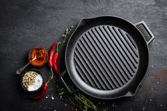 Empty cast-iron grill pan with ingredients for cooking on black background Stock Photo