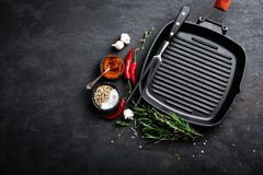 Empty cast-iron grill pan with ingredients for cooking on black background. Top view royalty free stock photos