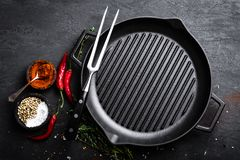 Empty cast-iron grill pan with ingredients for cooking on black background Royalty Free Stock Photo