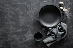 Empty cast-iron pan with cutlery on dark background for restaurant menu. Top view royalty free stock images