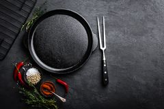 Empty cast-iron pan with ingredients for cooking on black background. Top view stock photography