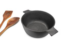 Empty Cast Iron Pot, Wooden Spatula And Serving Spoon Isolated royalty free stock photo