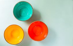 Empty ceramic colored bowls on a gray background. View from the top.Copy space. stock photo