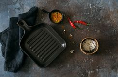 Empty ceramic pan and seasonings on dark grunge background. Top view.Copy space Stock Image