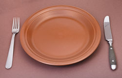 Empty ceramic plate with fork and knife on brown. Empty brown ceramic plate with fork and knife on brown background stock photos