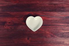 Empty ceramic saucer in the form of heart on a dark wooden table.  Stock Photos