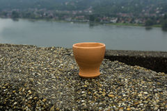 The empty ceramic shot glass. Costs on a wall against the river Stock Photos