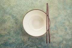 Empty ceramic soup plate. And chopsticks. Background with copy space. Selective focus. Toned image Stock Photo