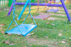 Empty chain and metal swings in playground and meadow grass fiel Stock Images