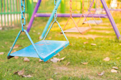 Empty chain and metal swings in playground and meadow grass fiel Royalty Free Stock Photography