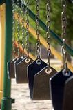 Empty chain swing. In a playground, shallow depth of field Royalty Free Stock Images
