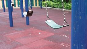 Empty chain swings in modern children playground in city. Sunny day.