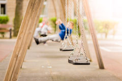 Empty chain swings in a playground. Blured background of swinging kids. Stock Photos