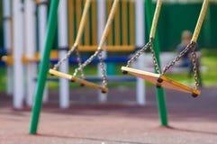 Empty chain swings on summer kids playground. Empty chain swings on summer playground Royalty Free Stock Image