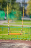 Empty chain swings on summer kids playground Stock Images