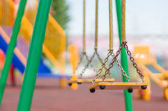 Empty chain swings on summer kids playground Royalty Free Stock Photo