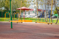 Empty chain swings on summer playground. Empty chain swings on summer kids playground Royalty Free Stock Images
