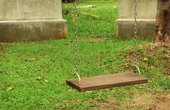 Empty chain wooden swings on activities yard in the public park royalty free stock images