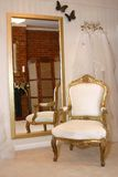 An Empty chair in dress shop. An Empty chaire in a wedding dress shop with veils on the wall Stock Image