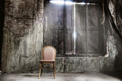 Empty chair and grungy wall. An empty chair and grungy wall on the background Stock Photos