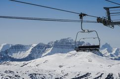 Empty chair lift above a snow capped mountain range royalty free stock image