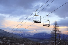 Empty Chair Lifts at a Ski Slope. Empty chair lifts suspended above the ground over a ski slope. Trees and mountains can be seen in the background under a cloudy Royalty Free Stock Photography