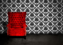 Empty chair in room. A red velvet chair in a dark room with antique wallpaper Royalty Free Stock Photography