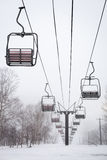 Empty Chairlift. Empty chair lift in the mist and snow at Niseko ski resort in Japan. Shallow depth of field Stock Photo