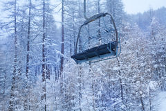 Empty chairlift against snow-covered forest Stock Photo