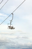 Empty chairlift with blue sky in the background Stock Images