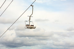 Empty chairlift with cloudy sky in the background Royalty Free Stock Photos